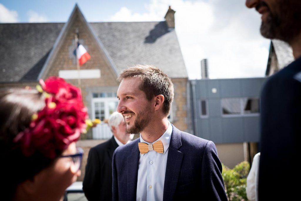 le marié retrouve les invités devant la mairie