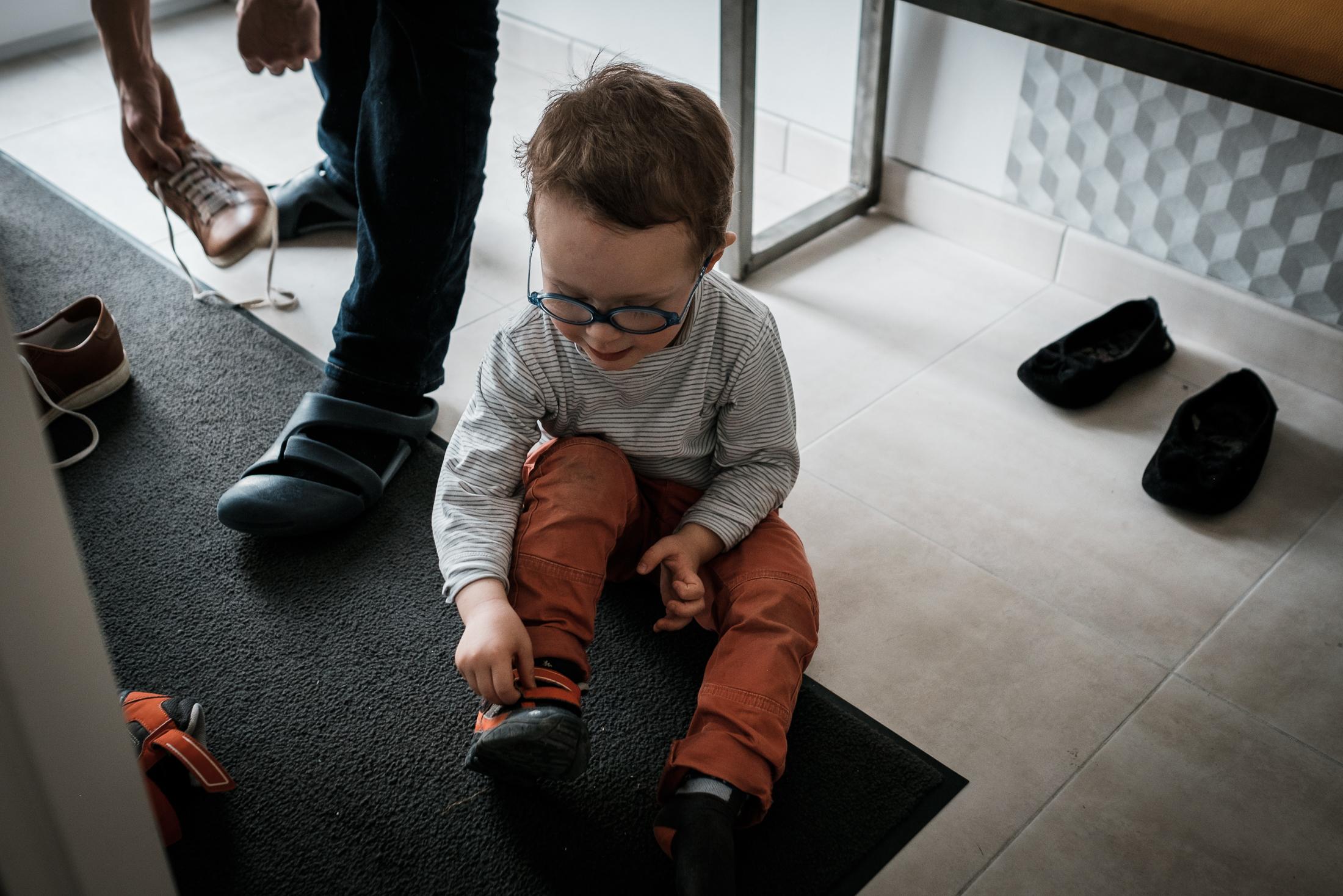 prestations photographe famille le petit garçon enlève ses chaussures