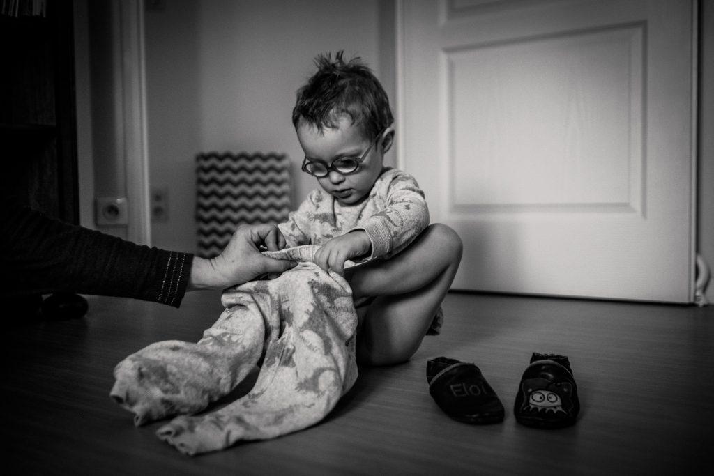 prestations photographe famille la maman aide le petit garçon à enfiler son pyjama