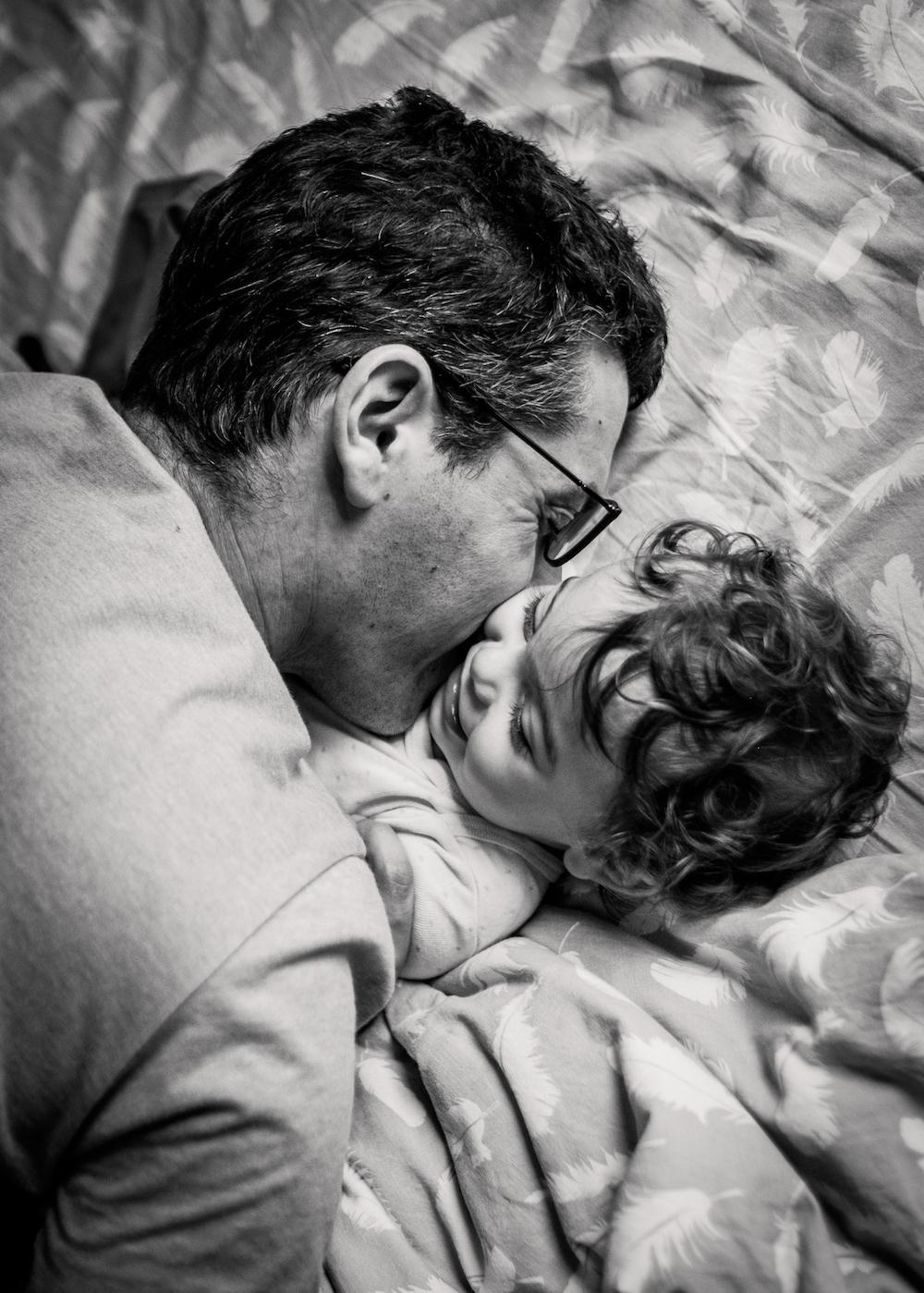 prestations photographe famille le papa fait un bisou dans le cou à son fils