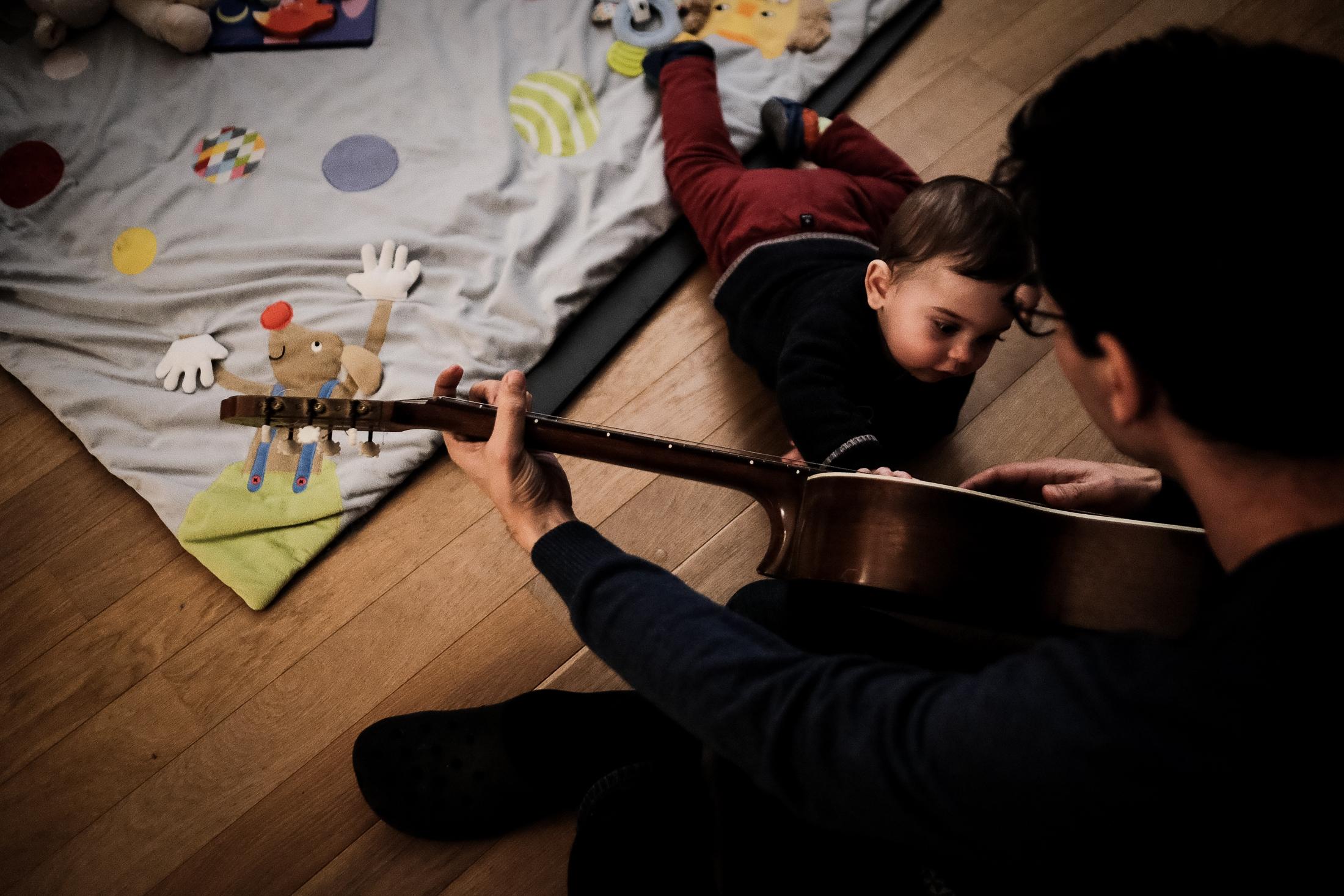 prestations photographe famille le papa joue de la guitare à son fils