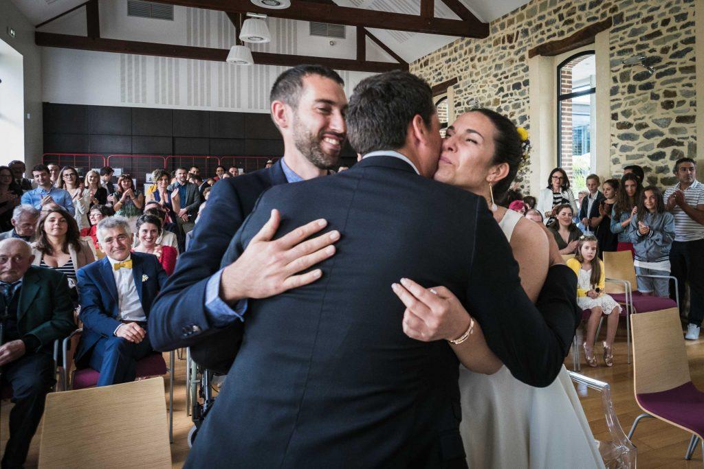 les mariés embrassent le témoin