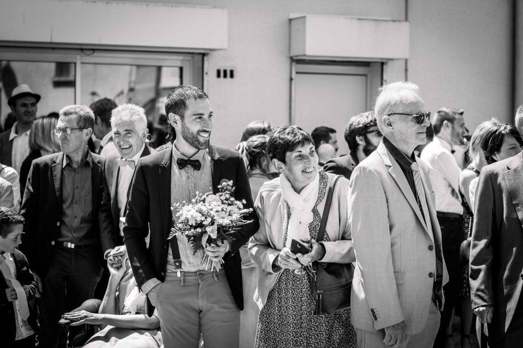 sourire du marié en voyant la voiture de la mariée arriver devant la mairie de saint aubin d'aubigné noir et blanc
