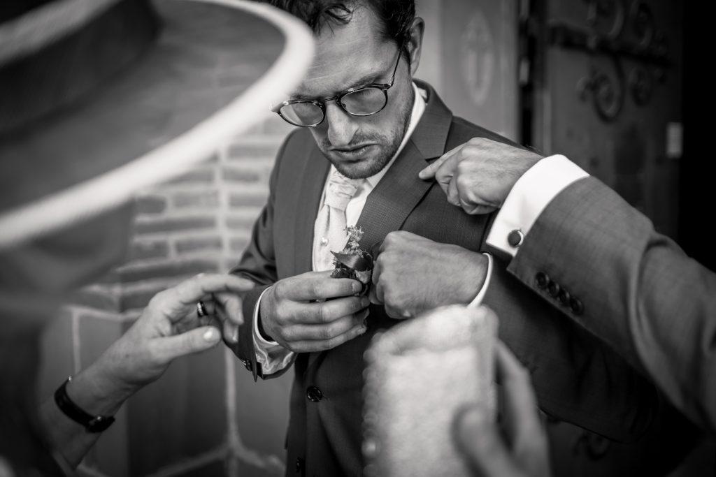le marié se fait aider pour mettre sa boutonnière
