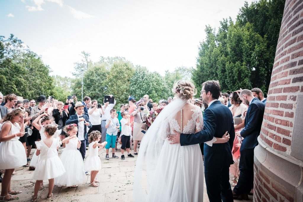 les mariés devant leurs invités à la sortie de la cérémonie