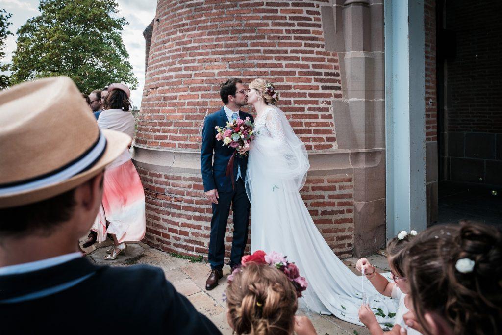 photographe mariage baiser des mariés à la sortie de l'église
