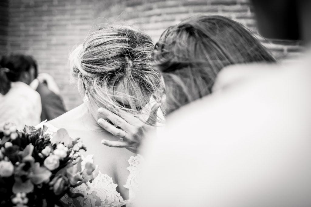la mariée émue devant une amie à la sortie de la cérémonie religieuse