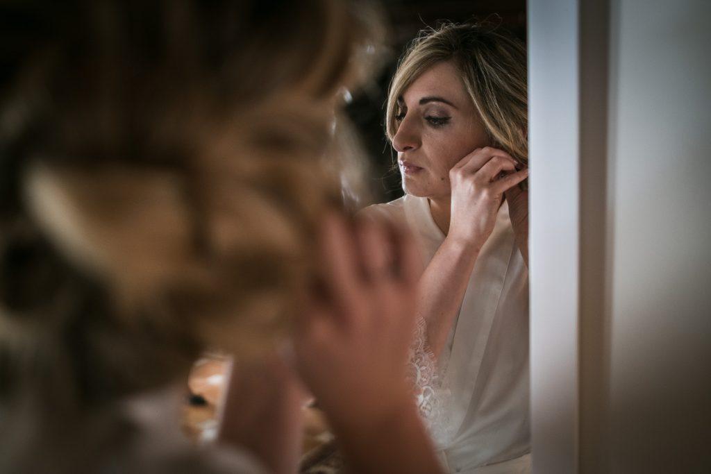 la mariée accroche ses boucles d'oreilles devant un miroir de l'annexe au château de mauriac