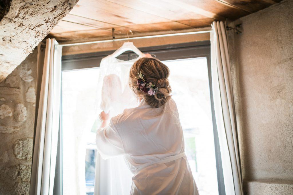 la mariée décroche sa robe de mariée dans l'annexe du chateau de mauriac