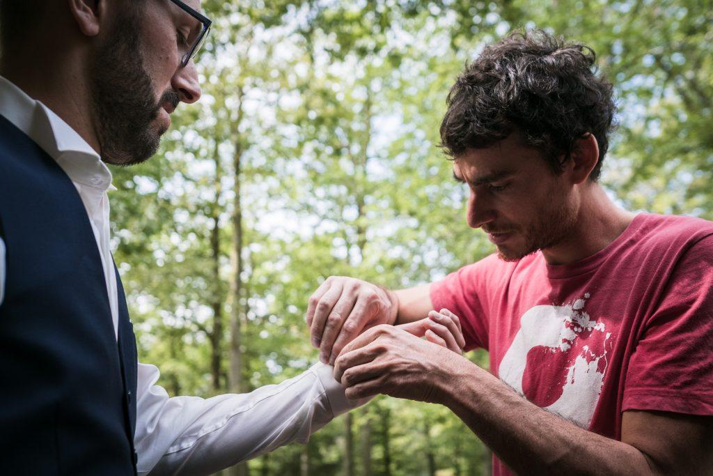 photgraphe mariage étangs de taysse le témoin aide le marié avec ses boutons de manchettes