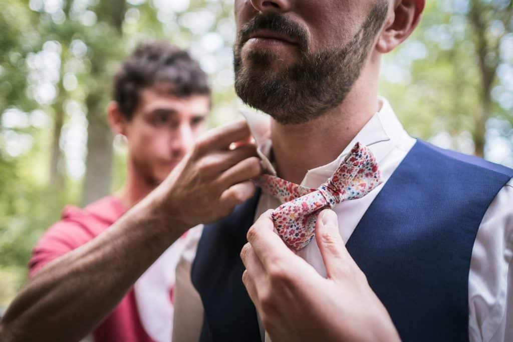 photographe mariage étangs de taysse le témoin aide le marié avec son noeud papillon fait main