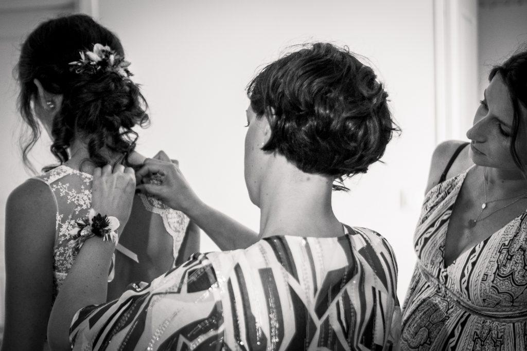 photographe mariage étangs de taysse la soeur et la meilleure amie aident la mariée à se préparer