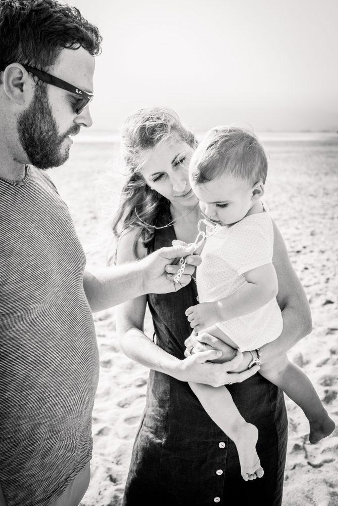 père mère et bébé à la plage noir et blanc