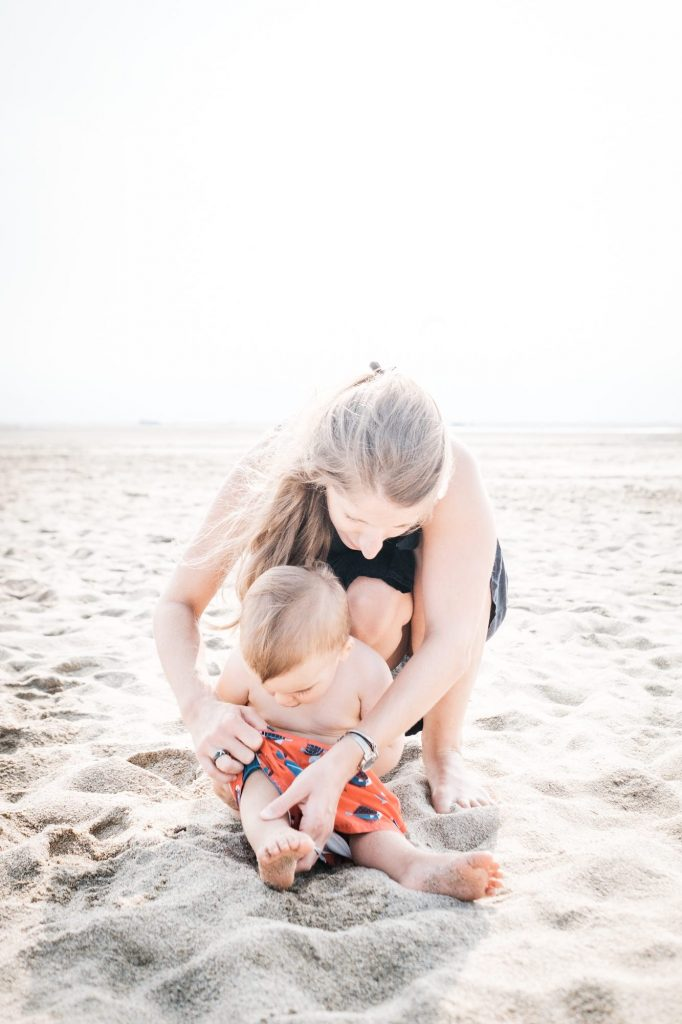 mom helps her baby to dress his bathing suit